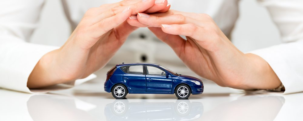 Hands covering small toy car show protection offered by individualized auto insurance ratings