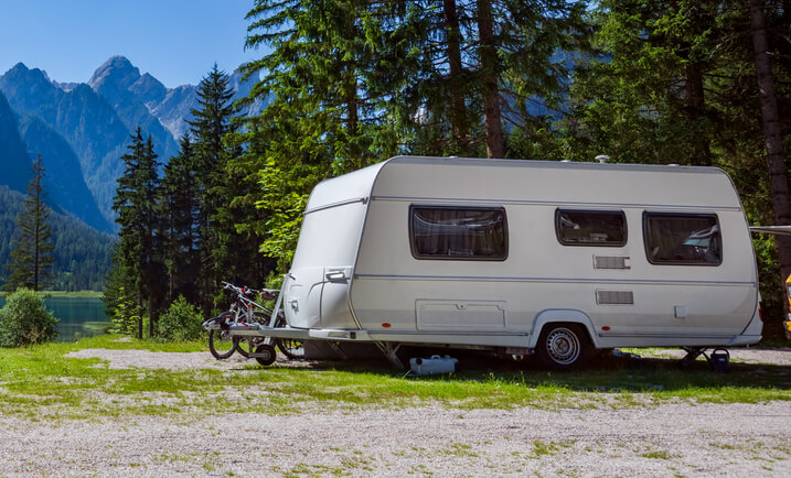 Do I Need RV Insurance? - RV parked in the woods by a lake